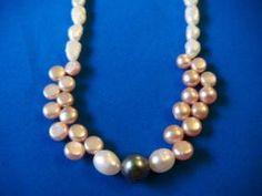 Finas perlas blancas con perla negra de centro