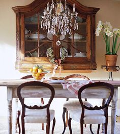 This casual dining area contains a late-1700s wall-hung cabinet showcasing a collection of white ironstone, which echoes the lines of the curvy Queen Anne chairs. The rustic farm table keeps the space down to earth.