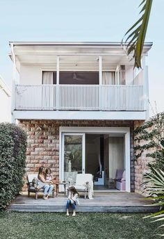Sandstone cladding and a crisp white balcony transformed the exterior of this Sydney beach house, with a silvered deck becoming the perfect outdoor entertaining area.