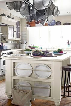 Farmhouse Design:  The kitchen island in this Ohio home boasts a zinc top crafted by a local metal shop and has a built-in plate rack for stealthy storage. Subway tile from Home Depot forms the backsplash.