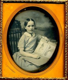 girl holds an open book of pictorial scenes