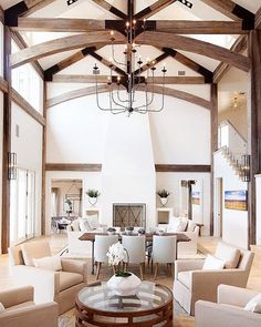 This lavish lakeside family home feels light and spacious, large wooden beams define the fabulous vaulted ceilings in the living room, and the soft color palette contrasts beautifully with the dark wood textures. Design by @tracyhardenburgdesigns #kathykuohome #interiordesign #livingroom #instahome #designlove #homedecor #rusticdecor
