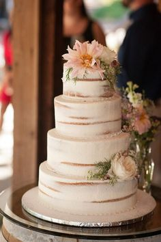 Semi naked Wedding cake topped with shabby chic flowers and greens.