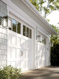 white garage doors with windows. Hardware on garage doors gives character and the illusion of two smaller doors. gray shingles and steel light fixtures,