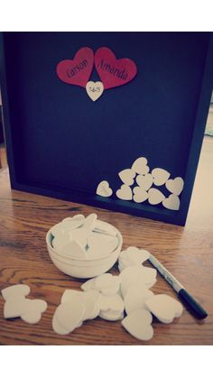 DIY guest book. In a shadow box place two hearts with the bride and grooms name then have guests sign smaller hearts with their name
