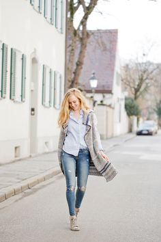 A sleveless knit cardigan and ripped jeans