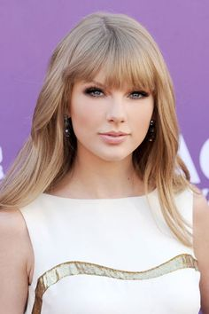 Taylor Swift's Beauty Transformation - 2012: Swift goes for a mature look with blunt bangs, and soft waves combined with her signature smokey eye and nude lip.