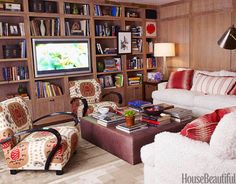 Designed by Peter Dunham, this media room/library is paneled in cerused oak, with sofas covered in Italian shearling, with Dunham's own red ikat fabric pillows.