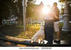 Boy and girl watching sunset with dog by Teksomolika, via Shutterstock