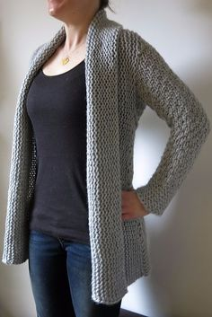 """""""Courie in"""" is a Scottish phrase meaning to """"snuggle up"""" - and it's the perfect name for this oversized, supremely warm, wrap front cardigan. This is a real winter warmer, ideal for nestling into with a mug of cocoa on a cold day. And it's so quick to knit! This cardigan has a slightly unusual construction. Sleeves are knitted first from cuff to centre back, then both sleeves are joined with a three needle bind off. Stitches are picked up at the bottom edge from armpit to armpit and worked…"""