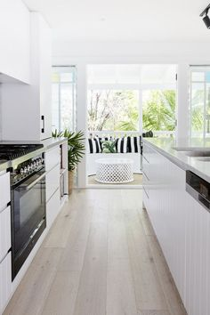 Simple modern kitchen. Light and airy. Black and white bold cushions. Light timber flooring.