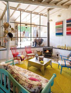 Visión de altura    Las butacas holandesas, pintadas por los Requejo, dan un singular toque al salón. La mesa de centro, de chapa de acero, diseño de Oito Interiores, y la gran alfombra es de Antonia Molina.
