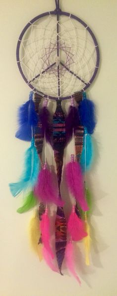 Handmade purple peace sign dreamcatcher with neon rainbow feathers and Aztec fabric