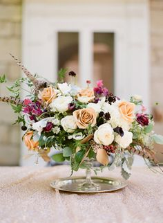 Renoir calla lily, Mona Lisa anemone, gold combo rose, and gold tipped succulent, air plant and feather arrangement by Molly Taylor Designs