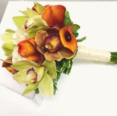 Bridal bouquet of green and brown cymbidium orchids, with rust orange calla lilies. Ballard Blossom Wedding Flowers. Seattle Florist.