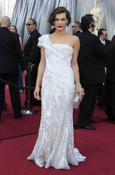 """Mila Jovovich, fantástica de Elie Saab, con un vestido blanco con pedrería, semi-palabra de honor, con un hombro y clutch a juego, ella lo define """"como algo sencillo, claro y estructurado""""."""