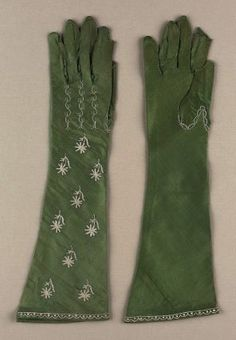 Pair of women's gloves French, early 19th century France MEDIUM OR TECHNIQUE Silk satin with silk embroidery and tambour-work Scalloped edge, decorative seams and small flowers on back of each hand and arm embroidered in chain stitch with cream-colored silk. One finger and thumb on each glove open at end.