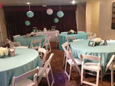 Room view. First Communion Party. Handcrafted tissue pom-poms in Light Blue, Light Green and White colors, hung by gold thread and adorned with sparkling, round clear crystals.