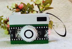 Caixa em formato de Máquina Fotográfica, produzida em papel 180gr. Possui elementos em 3d. <br>As cores podem variar de acordo com o gosto/necessidade do cliente. <br>Para quantidades maiores consulte-nos sobre prazos. <br>NO STUDIO SHANGRILÁ O CLIENTE É QUEM DEFINE A QUANTIDADE MÍNIMA!