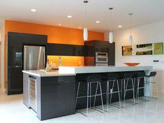 große kochinsel und ein paar schwarze barhocker und eine orange wand