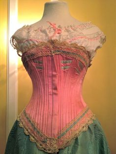 Circa 1898 pInk silk satin corset with blue bust trimming and ribbon insertion. Marked BALENA. Supported with 36 whale bones. 22″ waist. European. From the M. Talkington Collection.