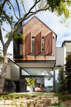 The rear extension on this modern house has an upper floor that cantilevers away from the house and provides shade for the small patio below.