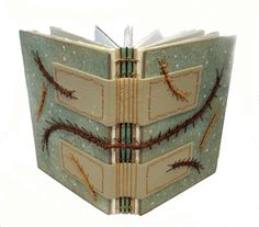 Journal with Centipede Stitch by Ann Renee Lighter. This book measures 5 x 7 inches and has 112 leaves of various weights and types of papers for both writing and illustrating or mixed media journaling. Leather hinges support a longstitch binding that leaves the spine partly exposed for interest. The covers are embellished with a multitude of centipedes all done in 4 ply waxed linen.