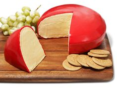 Cheese Wheel Cake : To make the look-alike, we rounded the edges of a basic layer cake and covered it with red fondant, then sliced out a wedge and spread the cut sides with pale yellow frosting. The finishing touch: We put the cake on a cheese board with cookies and sugared grapes.