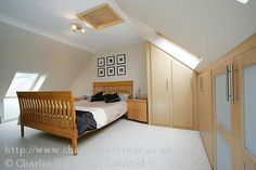 Master bedroom in attic conversion.  Like built in storage and sloping wall to floor with low window