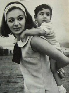 HRH Empress Farah poses for the camera as baby Ali rides 'piggy back'