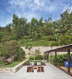Jacobsen Arq8. El jardín se integra a la perfección con el paisaje circundante, con vegetación típica de la zona y una piscina que se confunde con el verde de las plantas