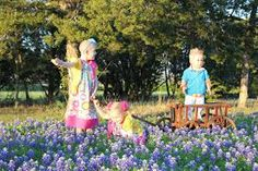 jaylie and her brother and sister playing in bluebonnets