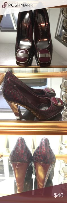 BCBGIRLS maroon pumps with buckle Gently used!!! Maroon snake skin like peep toe pumps. Only mark is on the one heel which is shown in picture. BCBGirls Shoes Heels