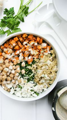 Healthy Kale Salad Bowl with Tahini, Roasted Sweet Potatoes, Quinoa, Feta, and Chickpeas.