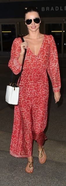 Who made Miranda Kerr's gold flat sandals, red print maxi dress, and white handbag?