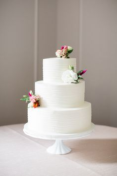 Textured + floral topped white wedding cake: http://www.stylemepretty.com/north-carolina-weddings/new-hill/2015/12/28/colorful-north-carolina-wedding/ | Photography: Robyn Van Dyke - http://www.robynvandykephotography.com/index2.php#/home/