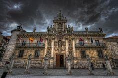 University – Universidad Valladolid (Spain) HDR  From the plaza de Santa María (today the University Square), one can see the interesting Baroque facade designed by the Carmelite Fray Pedro de la Visitación and constructed in 1715. There are distinct sculptural groups that represent allegories of the subjects that are taught in the building. The central section, organized into four columns of giants, is finished off by a giant ornamental comb (Wikipedia).