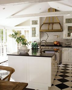 Classics -- checkerboard floors, brass hood detail, white framed cabinets -- this kitchen will never go out of style