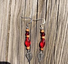 These beautiful earrings are handmade with silver leaf beads, red glass beads, and wooden beads. Each pair of earrings made by me are original and