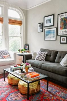 Rug, gallery wall, glass coffee table with pouffes