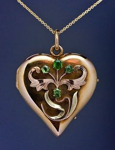 A polished yellow gold heart shaped locket is decorated with a chased rose and green gold Art Nouveau flower embellished with four Russian Uralian demantoid garnets. This locket was made in Moscow between 1899 and 1908.