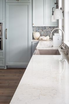 White stone kitchen countertops and pale blue cabinetry.