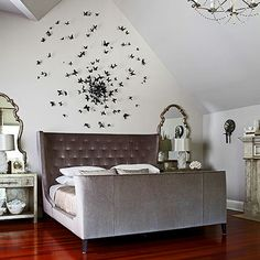 The butterfly wall sculpture by Paul Villinski is framed nicely by pairs of shagreen-like bedside tables, silver-leaf mirrors, and rock-crystal lamps.