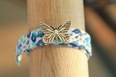 Bracelet biais type Liberty à fleurs bleues avec perle passante en forme de papillon : Bracelet par mon-atelier-a-bijoux