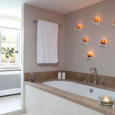 The marble around the top of the bath gives this bathroom a hint of luxury. Lights dotted around the wall create a romantic atmosphere and add warmth to the scheme.