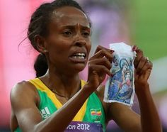 """Represent! Olympic gold runner Meseret Defar crosses the finish line and pulls a picture of the Virgin Mary with the Baby Jesus out from her jersey, shows it to the cameras and holds it up to her face in deep prayer. """"So whether you eat or drink, or whatever you do, do everything for the glory of God."""" 1 Corinthians 10:31"""