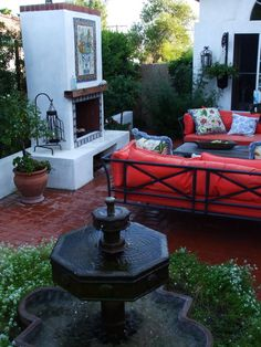 Spanish Courtyard/fountain Love red sofas with outdoor fireplace.
