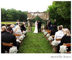 The perfect backdrop for the ceremony! An arbor made out of branches with burlap tied back with flowers. And it doesn't hide the beautiful scenery. // Photography: Marielle Hayes Photography // Cinematography: Hampton Road Studios // Styling:  Big Events Wedding