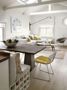 salon design dans un loft avec peinture murale blanche, canapé d'angle blanc avec coussins en jaune et gris et coin repas avec table en bois et banc avec rangement