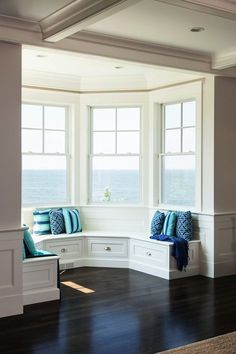 Lewis and Weldon - living rooms - builtin window seat, window seat, curved window seat, window seat with storage, blue pillows, turquoise pi...